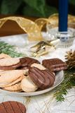Cookies, blue candle, fir branch, ornaments and pine cone on hol. Some cookies, small fir branch , pine cone,  blue candle and Christmas ornaments are set on Stock Photo