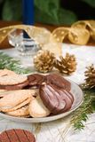 Cookies, blue candle, fir branch and pine cones on holiday napkin. Some cookies, small fir branch , pine cones, blue candle and Christmas ornaments are set on stock photography