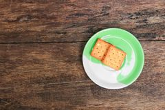 Cookies bread square in the plate on old wooden floor background.  stock images