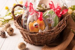 Cookies in a brown wicker basket near quail eggs and blossoming branch royalty free stock photos