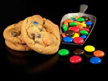 Cookies and Candy. Three candy, chocolate chip cookies with a scoop of colorful coated candy on a black background Stock Image