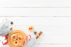 Cookies, candy cane and Christmas decorating items on white wood Royalty Free Stock Photography