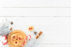 Cookies, candy cane and Christmas decorating items on white wood Stock Photo
