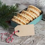 Cookies with caramel cream and walnuts in a vintage metal box, Christmas decoration and a clean, empty tag on bright wooden surfac Stock Photos