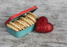 Cookies with caramel cream and walnuts in a vintage metal box, decorative red heart on bright wooden surface. Royalty Free Stock Images
