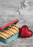 Cookies with caramel cream and walnuts in a vintage metal box, decorative red heart on bright wooden surface. Stock Images