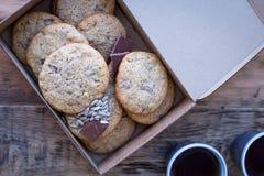 Cookies caseiros da farinha de trigo inteiro com chocolate e sementes, em uma tabela de madeira em uma caixa de cartão fotografia de stock