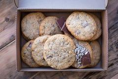 Cookies caseiros da farinha de trigo inteiro com chocolate e sementes, em uma tabela de madeira em uma caixa de cartão imagens de stock royalty free