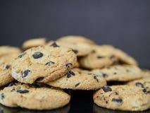 Cookies caseiros dos pedaços de chocolate no fundo do preto escuro ou do cinza Fotografia de Stock Royalty Free