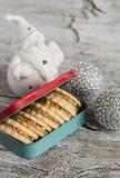 Cookies caseiros na caixa do vintage, decorações cerâmicas de Santa Claus e do Natal em uma superfície de madeira Fotografia de Stock