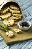 Cookies with cheese, olives and rosemary. Homemade cookies with cheese, olives and rosemary, cup of olives and rosemary branches on linen napkin on wooden rustic Royalty Free Stock Image