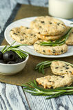 Cookies with cheese, olives and rosemary on napkin Stock Photo