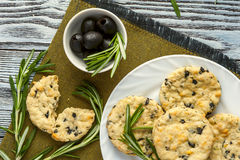 Cookies with cheese, olives and rosemary on napkin. Homemade cookies with cheese, olives and rosemary on white plate, cup of olives, rosemary branches on linen Stock Image