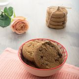 Cookies with chocolate in a beautiful bowl. A delicate rose with cappuccino. A bunch of biscuits tied with scoop, bokeh. In the background. A gentle romantic stock image