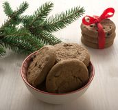 Cookies with chocolate in a beautiful bowl, next to a spruce branch. A bunch of cookies tied with a red ribbon, a bokeh. In the background. A gentle romantic stock photos
