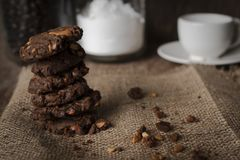 Cookies chocolate of cashew nut are arranged on a sack the cup of coffee, bottle of flour, bottle of coffee behind royalty free stock photography