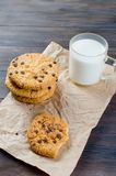 Cookies with chocolate drops and a glass of milk. Cookies with chocolate drops  on craft paper and a glass of milk on dark wooden background. copy space Stock Photo