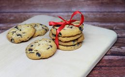Cookies with chocolate. Festive cookies with chocolate and red bow on a wooden board Royalty Free Stock Images