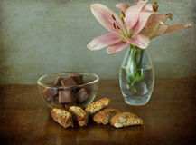 Cookies, chocolate and flowers. Chocolate candies and italian almond cookies (cantucci) on a desk with a vase of pink lilies on a grunge and vintage background vector illustration