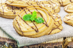 Cookies with chocolate lines on linen and wood Stock Photos