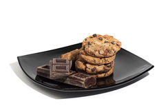 Cookies and chocolate pieces on black plate, isolated on white Royalty Free Stock Photography