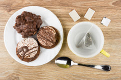 Cookies with chocolate in plate, cup with teabag, sugar Royalty Free Stock Images
