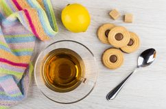 Cookies with chocolate stuffed, sugar, lemon, cup of tea, napkin. And teaspoon on wooden table. Top view Royalty Free Stock Images