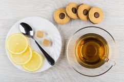 Cookies with chocolate stuffed, sugar, lemon, teaspoon, tea. Cookies with chocolate stuffed, sugar, lemon and teaspoon on plate, cup of tea on wooden table. Top Stock Photography