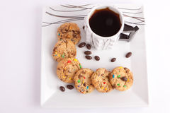 Cookies and chocolate with tea. Cup of tea with cookies staffed colored chocolate and chocolate on white stock image
