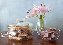 Cookies, chocolates and flowers on a wooden table Royalty Free Stock Image