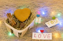 Cookies and chocolates in the form of heart. Basket with hay. Multicolored lights. Royalty Free Stock Photography