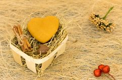 Cookies and chocolates in the form of heart. Basket with hay. Royalty Free Stock Images