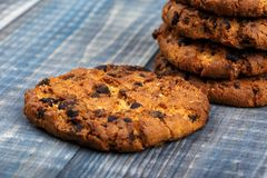 Cookies with chunks of chocolate. Close-up. Selective focus. In the background a column with biscuits royalty free stock image
