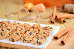 Cookies and cinnamon sticks on table. Cookies on a cutting board and a kitchen towel. near are cinnamon sticks. horizontal Royalty Free Stock Photo