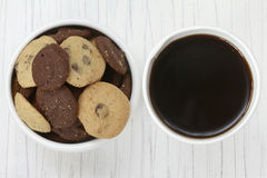 Cookies and Coffee. Top view of a bowl of cookies and a cup of coffee on a textured surface Stock Photos