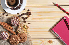 Cookies, coffee and notepad on a table royalty free stock photo
