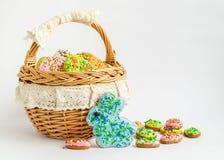 Cookies coloridas da Páscoa em uma cesta Imagens de Stock