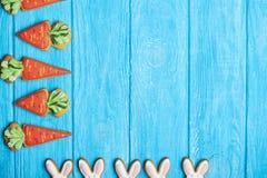 Cookies coloridas do coelho de easter no fundo de madeira azul Fotos de Stock