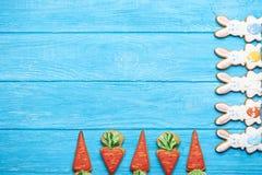 Cookies coloridas do coelho de easter no fundo de madeira azul Imagem de Stock