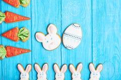 Cookies coloridas do coelho de easter no fundo de madeira azul Fotografia de Stock Royalty Free