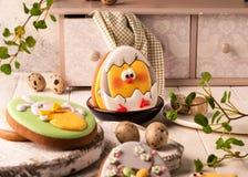Cookies com coelhinho da Páscoa e a galinha pintados perto do bufete decorativo e guardanapo verde nas placas de corte brancas imagem de stock