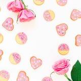 Cookies com esmalte cor-de-rosa e rosas no fundo branco Composição do amor Configuração lisa Vista superior Imagem de Stock Royalty Free