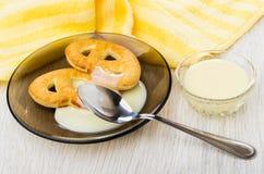 Cookies com leite condensado, guardanapo, leite na bacia na tabela fotos de stock