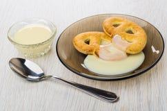 Cookies com leite condensado nos pires, leite na bacia, colher imagem de stock