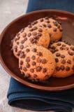 Cookies com pedaços de chocolate em uma placa marrom em um guardanapo branco fotos de stock royalty free