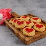 Cookies com um enchimento coração-dado forma em uma placa decorativa de madeira Conceito para o dia do ` s do Valentim fotografia de stock