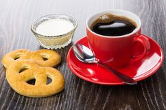 Cookies, copo vermelho com café, colher, leite condensado na bacia fotografia de stock royalty free