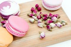 Cookies cor-de-rosa deliciosas francesas dos macarons da cor e rosas pequenas na mesa de madeira Imagem de Stock Royalty Free