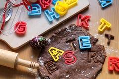 Cookies cortadas da massa crua do chocolate em uma tabela de madeira com letras coloridas Cozinhando biscoitos tradicionais da P? fotografia de stock
