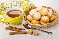 Cookies with cottage cheese filling in basket, tea, cinnamon, su. Heap of cookies with cottage cheese filling in wicker basket, cup of tea, cinnamon sticks Stock Images